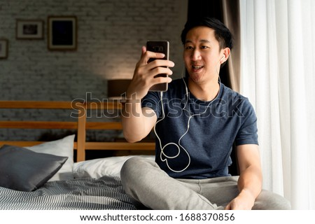 Portrait of happy 30s aged Asian man in casual clothing making facetime video calling with smartphone at home. He's waving at people on phone screen. Using conferencing meeting online app concept #1688370856