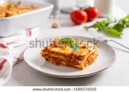 Piece of tasty hot lasagna served with a basil leaf on a gray plate. Italian cuisine, menu, recipe. Homemade meat lasagna. Close up, side view #1688376010
