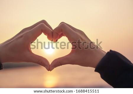 Woman hand do heart shape on sunset sky and bokeh background.