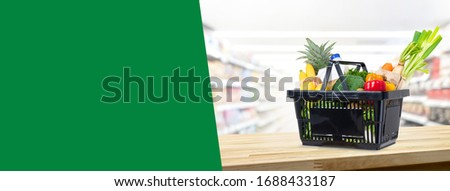 Shopping basket full of groceries on wood counter in supermarket background banner with copy space for text