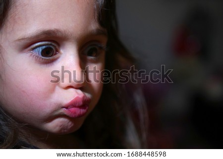 Pretty little girl with big eyes make funny faces, with copy space #1688448598