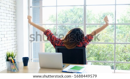 Work from home, Stretch for relax, Young asian woman stretching body while working with laptop computer at her desk home office, Back of female student raised arms take rest from online education #1688449579