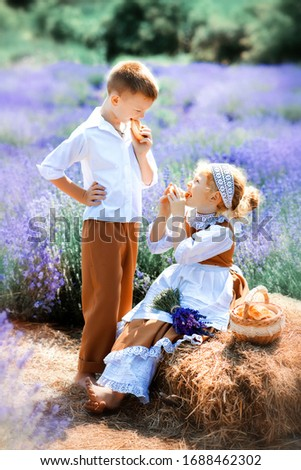 Vertical picture of children in vintage clothes in middle of lavender field. Girl in brown dress with white apron and boy in white hat, shirt and brown trousers have picnic on lavender. Eating outdoor