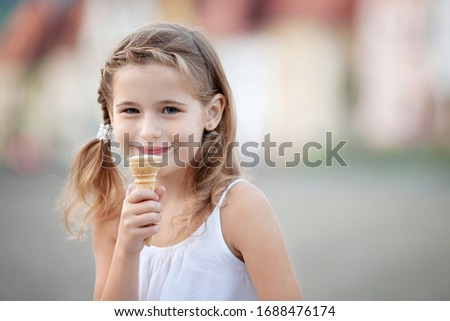 Beautiful smiling little girl eating ice-cream in waffles cone in the summer. Copy space  #1688476174