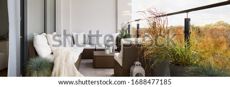 Panorama of elegant decorated balcony with rattan outdoor furniture, bright pillows and plants Royalty-Free Stock Photo #1688477185