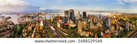 North SYdney and North shore suburbs along multi-lane motorway leading to the Sydney harbour bridge and CBD in wide aerial panorama. Royalty-Free Stock Photo #1688529568