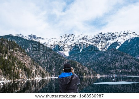 A man in a black jacket with a blue hood and a baseball cap takes a picture of a beautiful mountain landscape. Lake Ritsa in the spring season. Located in Abkhazia, in the mountains of the Caucasus.