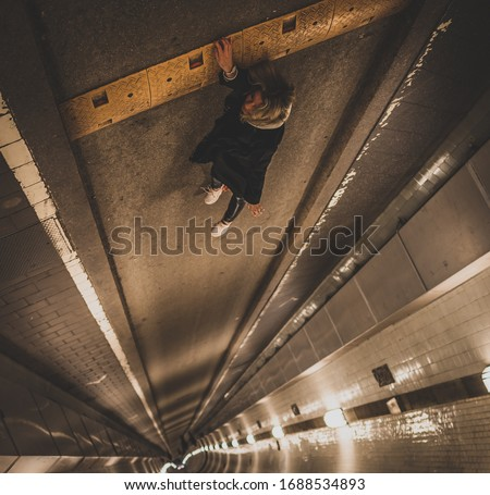 Optical illusion of a woman falling down while holding with her hand Royalty-Free Stock Photo #1688534893