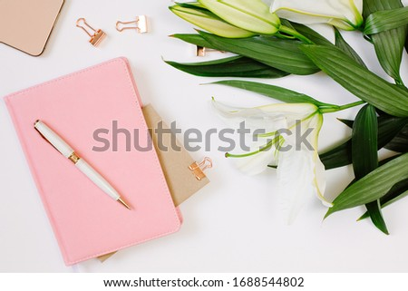 Beautiful fresh white lily and notebook with blank page on white background. Mood blogging concept #1688544802