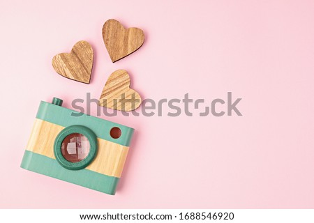 Flat lay with toy wooden camera and hearts over pink background. Social media, posts, likes, followers, online photography classes concept. Top view, copy space.