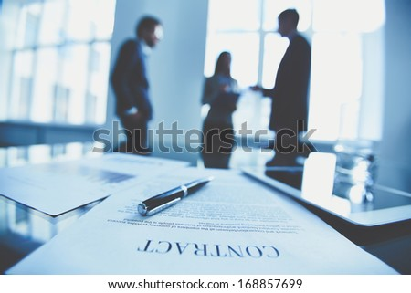 Close-up of business contract with pen at workplace on background of office workers interacting Royalty-Free Stock Photo #168857699