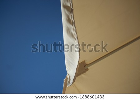 Up into the fabric umbrella canopy of a sun screen in front of a clear blue sky in Tenerife #1688601433
