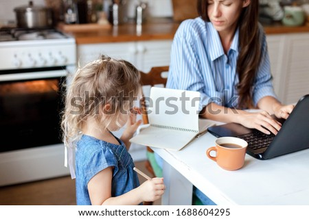 Working mom works from home office with kid. Stressed woman using laptop. Child drawing, spoiling mother notebook. Freelancer workplace in kitchen. Remote female business, career. Lifestyle moment