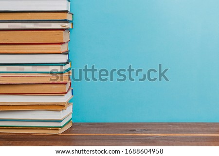 A simple composition of many hardback books, raw books on a wooden table and a bright blue background. back to school. Education. #1688604958