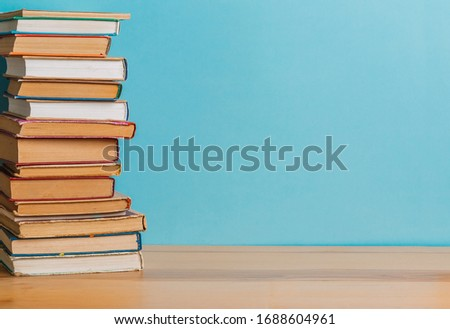 A simple composition of many hardback books, raw books on a wooden table and a bright blue background. back to school. Education. #1688604961