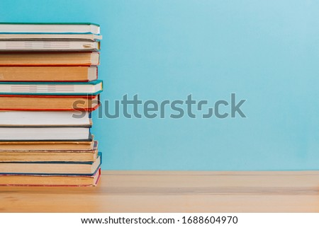 A simple composition of many hardback books, raw books on a wooden table and a bright blue background. back to school. Education. #1688604970
