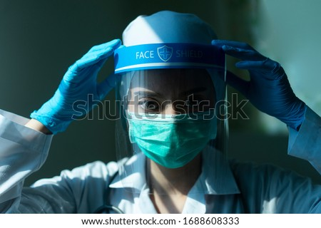 Closeup Asian female Doctor wearing face shield and PPE suit for Coronavirus outbreak or Covid-19, Concept of Covid-19 quarantine #1688608333