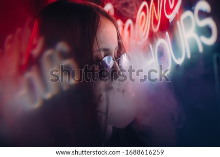 girl in glasses in a neon light among smoke. girl on a night street in purple light of a neon sign. life of the night city. neon lights at night. night woman portrait. fashion model posing in neon