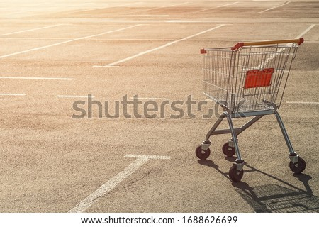 Single abandoned empty shopping trolley in an empty parking lot near a supermarket in the absence of people at sunset. #1688626699