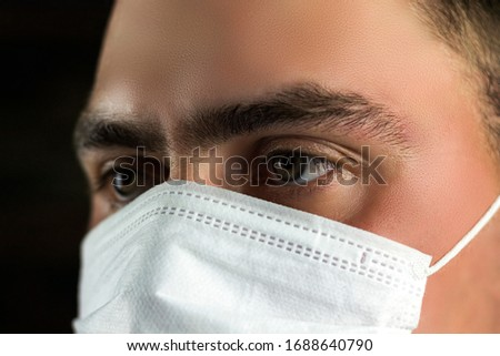 young man in medical mask on a dark background #1688640790