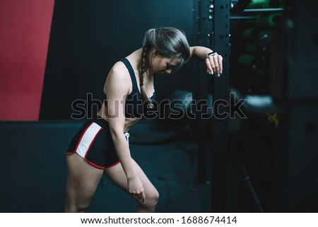 Side view of fit female in shorts and bra leaning on rack with equipment and panting while resting during break in workout in gym #1688674414