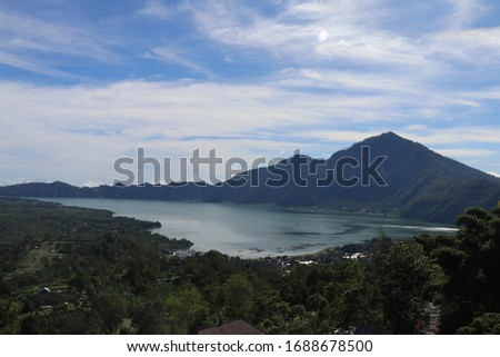 Mountain lake in the volcanic caldera of Batur under Mount Abang on the island of Bali, Indonesia. Quiet level of a large drinking water reservoir. High mountain peaks rise above the lake. Blue sky. #1688678500