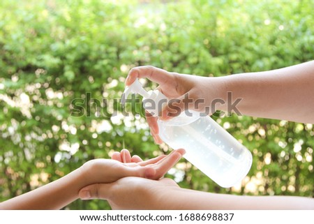 Mom using alcohol gel for cleaning baby hands. Concept of fighting and protecting with coronavirus from WHO. COVID-19. Copy space. #1688698837