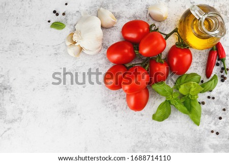Fresh colorful tomatoes, basil and olive oil on white table. Top view with copy space #1688714110