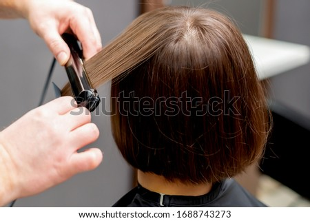 Hairdresser straightens hair of woman with hair straightener tool in hair salon. #1688743273