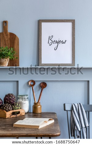Stylish composition of kitchen interior with wooden family table, vegetables, herbs, food supplies, mock up photo frame and kitchen accessories in gray concept of home decor.