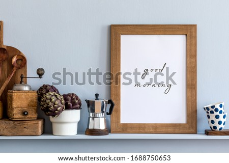 Modern composition on the kitchen interior with mock up photo frame, wooden cutting board, coffee percolator, vegetables and kitchen accessories in stylish home decor.