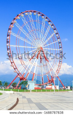 Ferris Wheel against the blue sky with clouds in the Resort Town, Sunny Day. Rotating Ferris wheel with cabins or capsules and center part. Concept of lifestyle, fun, growth, relax. Vertical photo. Royalty-Free Stock Photo #1688787838