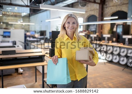 At workshop. Blonde woman holding boxes and paper packege, smiling #1688829142
