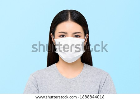 Asian woman wearing medical face mask isolated on light blue background #1688844016