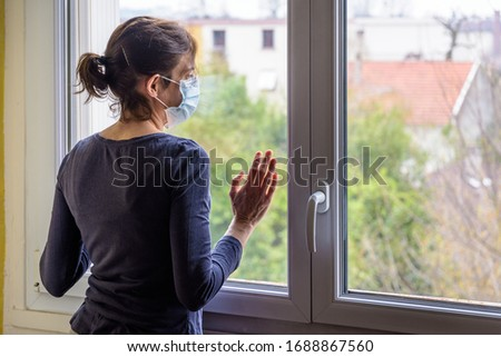 A woman under quarantine at home, wearing a medical face mask and a casual outfit, is standing idle in front of a closed window, the hand on the glass, staring into space. #1688867560