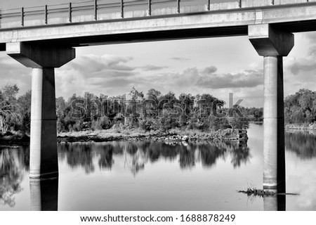 Black and white capture of a long concrete bridge, shot taken below the bridge on the river,   
