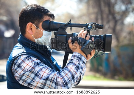 A videographer of a local television station shoots a video in an antivirus mask because of the corona of the virus