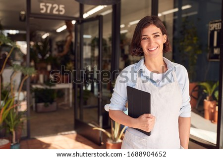 Portrait Of Female Owner Of Florists With Digital Tablet Standing In Doorway Surrounded By Plants Royalty-Free Stock Photo #1688904652