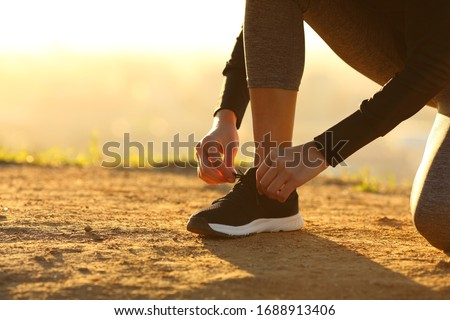 Closeup of runner woman hands tying shoelaces of shoes on the ground at sunset #1688913406