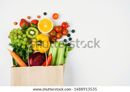 Fruits and vegetables on a light background in a Kraft bag from the store. Healthy and healthy food from the farmers ' market. Space for text #1688913535