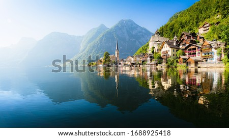 Scenic panoramic view of famous Hallstatt lakeside town reflecting in Hallstattersee lake in the Austrian Alps in scenic morning light on a beautiful sunny day in summer, Salzkammergut region, Austria #1688925418
