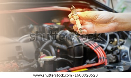 Hand holding a used spark plug,Motorcycle Maintenance and Repair. #1688928523