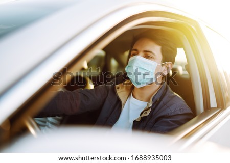 Young man in protective sterile medical mask driving car. The concept of preventing the spread of the epidemic and treating coronavirus, pandemic in quarantine city. Covid -19. #1688935003