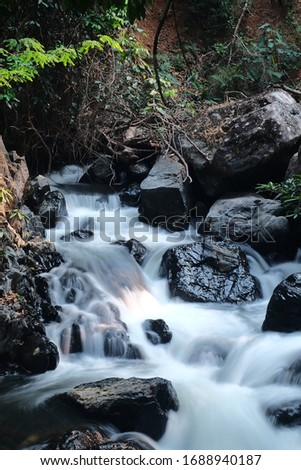 Natural waterfall In the hot season, northern Thailand Mae Hong Son province Natural tourism, traditional forests, holidays with cool running water, sunlight, waterfalls, green trees #1688940187