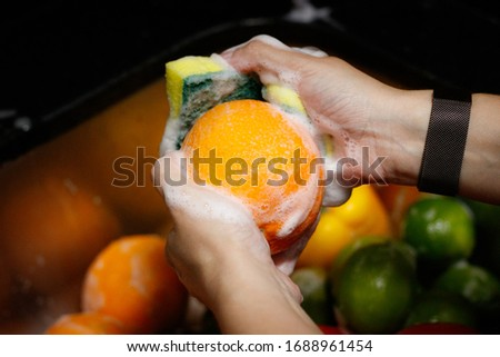 Washing the fruits and vegetables. The picture shows a variety of fruits and vegetables being washed with soap and water.