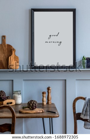 Interior design of kitchen space with black mock up photo frame, wooden table, chairs, herbs, cutting board, food and kitchen accessories in modern home decor.