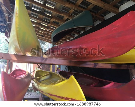 Colorful picture of canoes in a wooden canoe / kayak rack. There are yellow, red and dark green canoes creating a beautiful view suitable for camping concept walpapers.