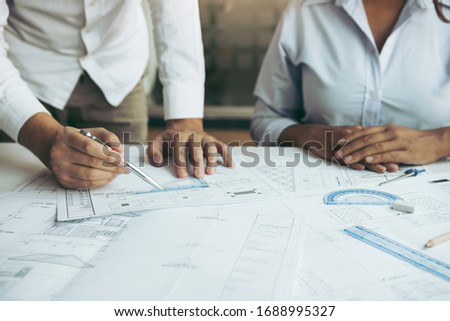 Two architect working at construction site and compass drawing pointing on blueprint with partnership.