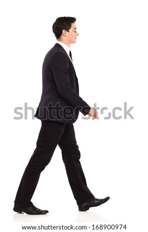 Smiling young businessman walking in black suit. Full length studio shot isolated on white. #168900974