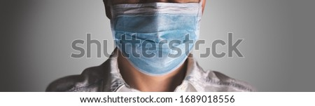 Doctor wearing protection face mask against coronavirus. Banner panorama medical staff preventive gear. #1689018556